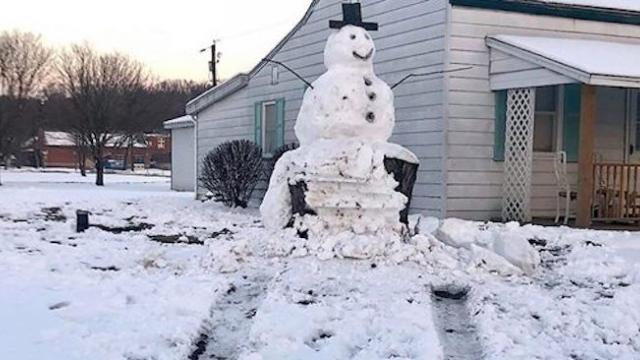 Couple's giant snowman built on tree trunk base teaches rude driver a lesson in karma