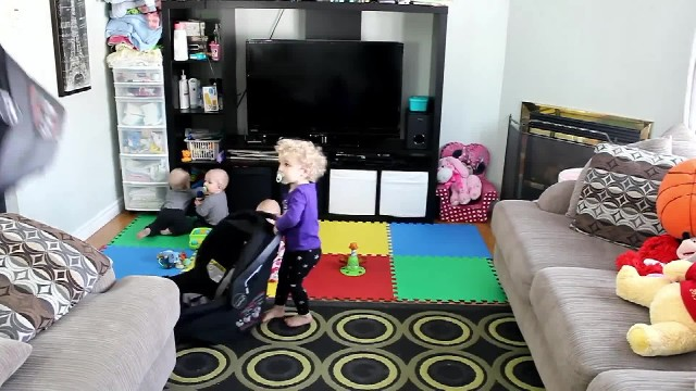 Mommy's trying to load triplets in car seats but her toddler's ulterior motives have everyone losing