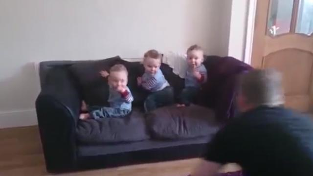 Triplets wait quietly on couch, but excitement is through the roof when dad comes home