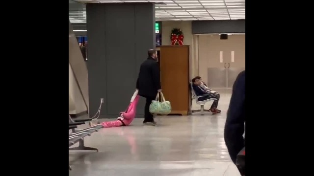 Hilarious moment father drags daughter through airport by her hood