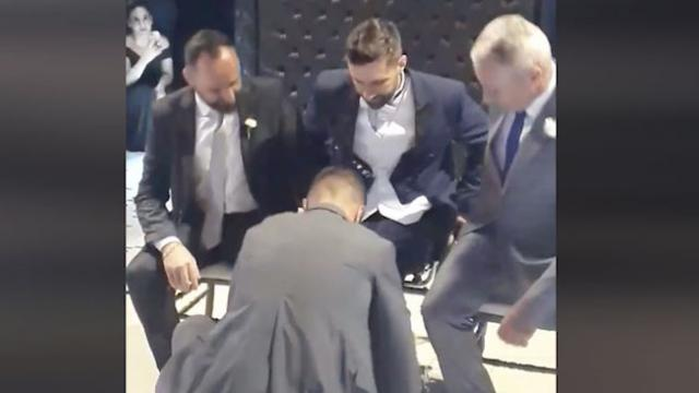 Wedding guests weep tears of joy as groomsmen help paralyzed groom dance with bride.