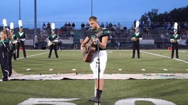 Nobody was there to sing the National Anthem, so he took off his helmet and grabbed the guitar