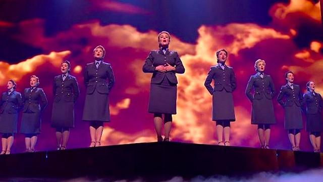Crowd's in awe as women sing WWII llassic erupting when special guests arrive on stage