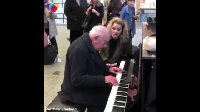 Elderly man plays piano in train station when lady jumps in to sing making crowd stop in their track