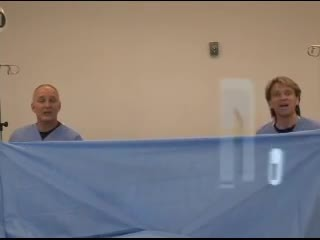 5 nurses stand behind a sheet. Once they come out from behind, they have everyone in stitches.