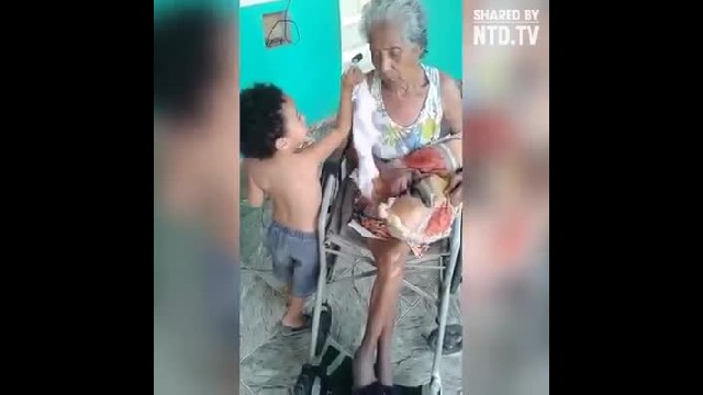 Little boy feeds his grandmother who can't feed herself with love and care