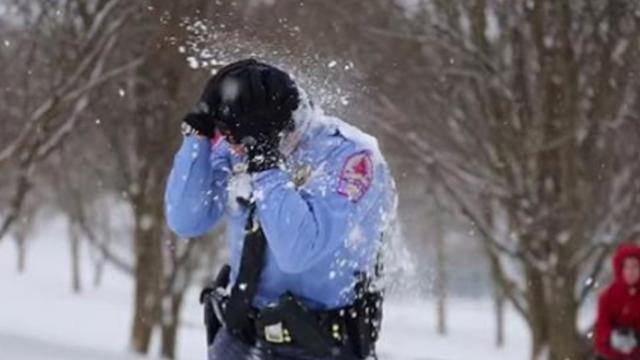 Police officers get bombarded by snowballs and decide to join in on the fun