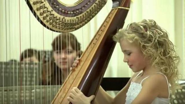 Nine-year-old sits with a harp, but when the music starts, everyone in the room is floored