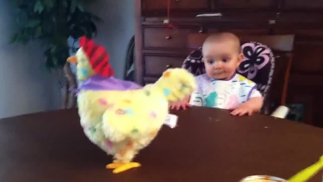This baby girl is unfazed by her toy hen— until it starts laying eggs