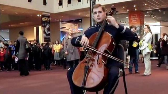 Lone soldier begins playing only to be rushed by 120 musicians giving shoppers memory of a lifetime