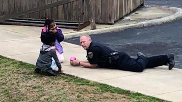 Officer responding to emergency call plays on ground with dolls to help keep kids calm