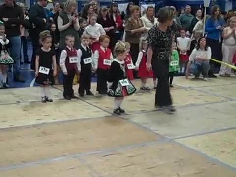 3-year-old impatiently waits her turn on stage. Her Irish step dance has everyone cheering