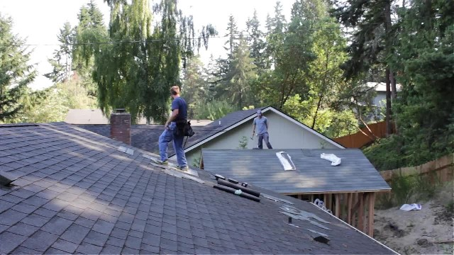 Roofers are working when music comes on. Man in blue quickly brightens everyone's day