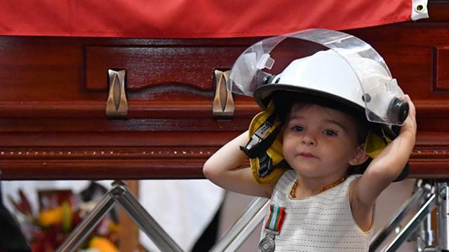 1-year-old girl wears her Australian firefighter dad's helmet and refuses to leave his side at his f