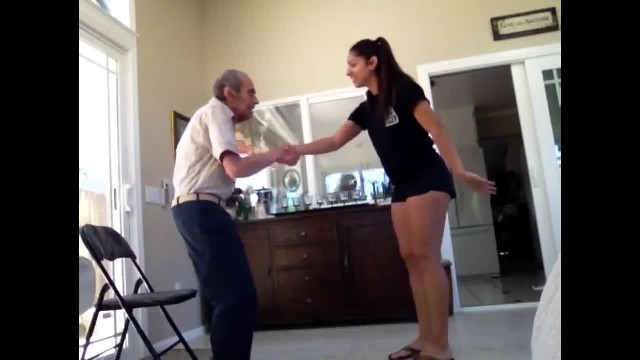Young woman holds out hand to grandpa. In no time their dance moves win over the internet