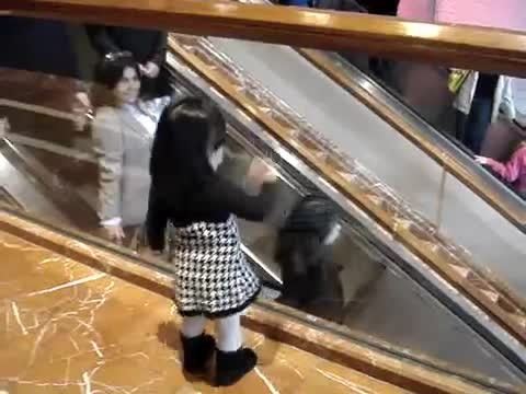 Tiny girl waves at strangers on the escalator but it's how they respond that surprises even dad