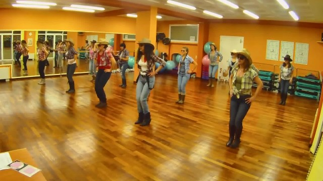 Cowgirls kick up their heels in boot-stompin' Brooks & Dunn line dance