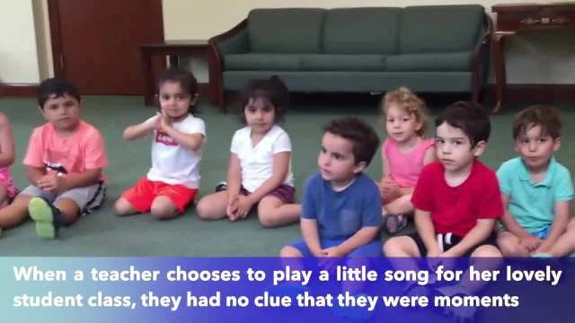 A cute little boy can't stop laughing as his teacher plays the guitar
