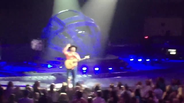 Garth Brooks distracted by woman waving sign only to read it and immediately walk off stage