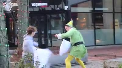 "Firefighter Dresses Like ""Elf"" & Challenges Strangers To Pillow Fights In Funny Video"