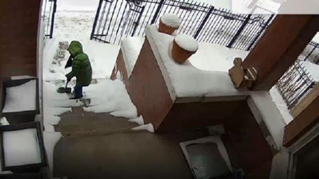 8-year-old Chicago boy helps out by shoveling his house's steps while ups driver dad is at work