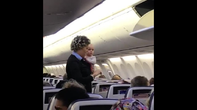 Adorable baby girl blows kisses at passengers after flight attendant scoops her up