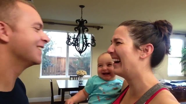 "Daddy tries to steal a kiss from mommy but baby's ""intervention"" has them losing it"