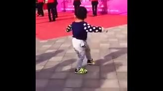 Toddler stops to watch dancers then steals the show when he quickly flips around