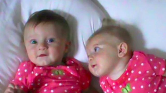 Mommy lays twins side by side on bed but take note of the baby