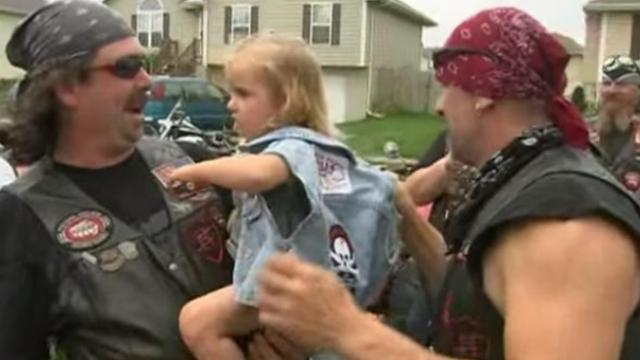 A whole gang of tough bikers surround a child to protect her