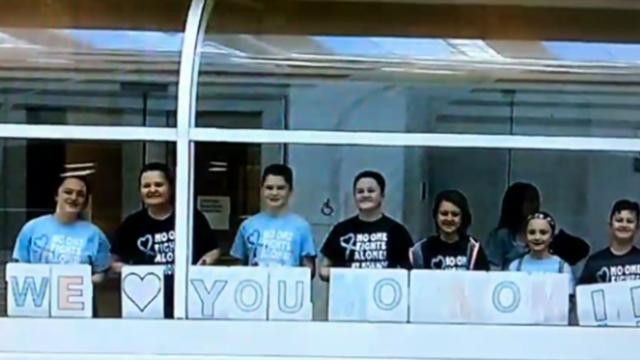 Grandma battling brain cancer looks out window and sees grandkids holding up sweet sign