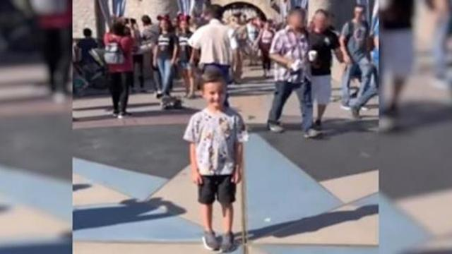 Boy's posing at Disneyland when strangers notice man sneaking up on him through crowd