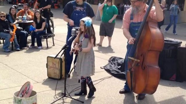 Tiny girl strums ukulele and sings. Passersby stop in their tracks when they hear her voice.