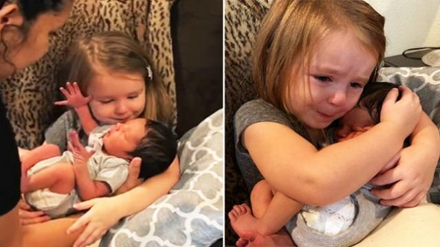 Tears well up in little girl's eyes as she cuddles newborn baby
