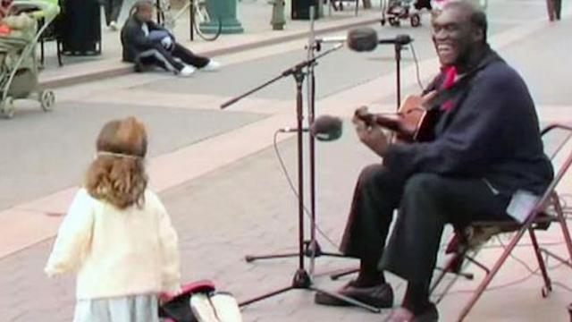 This street performer starts playing a classic I can't stop smiling