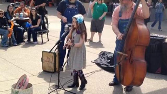 Girl strums ukulele and sings. Passersby stop when they hear her voice