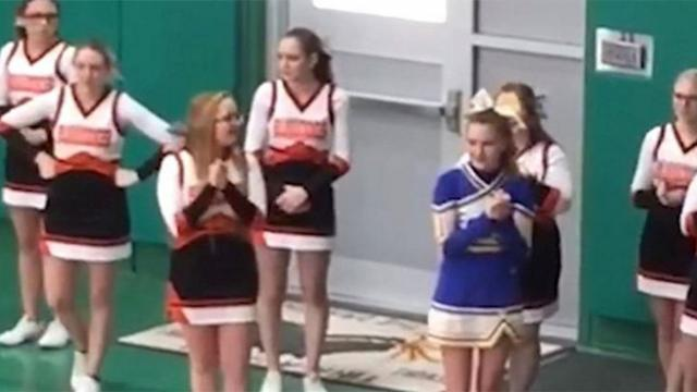 Cheerleaders surround girl from rival team Their actions are