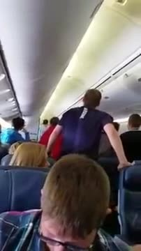 Military private carries fallen soldier's remains off plane. Then suddenly people begin to stand up.