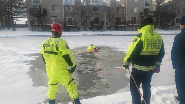 New footage shows chilling moment rescuer swims across ice to save trapped golden retriever