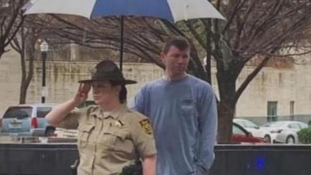 Stranger holds umbrella for deputy paying tribute in the rain to fallen comrade