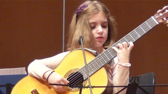 This little girl is as big as the guitar is playing—but her skills are larger than life!