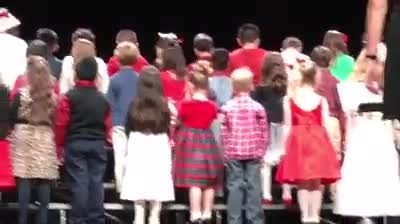 Kids line up onstage as they turn around girl in red dress has audience rolling