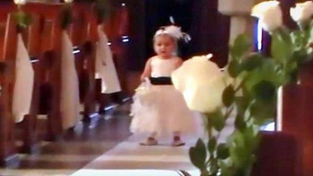 Bride's about to make her entrance until flower girl has guests rolling in seats