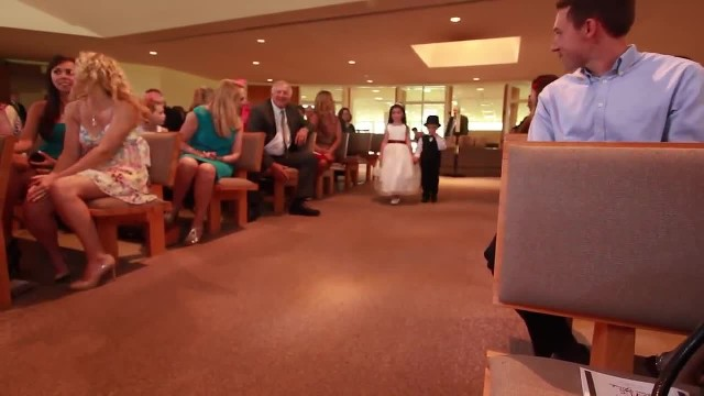Small ring bearer takes position but quickly his entrance has guests rolling with laughter