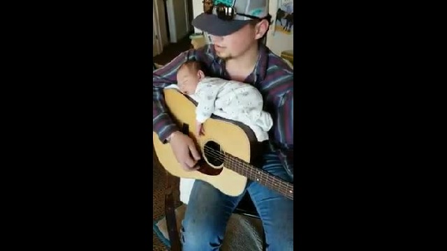 Country singer puts newborn daughter to sleep by sitting her on guitar and playing