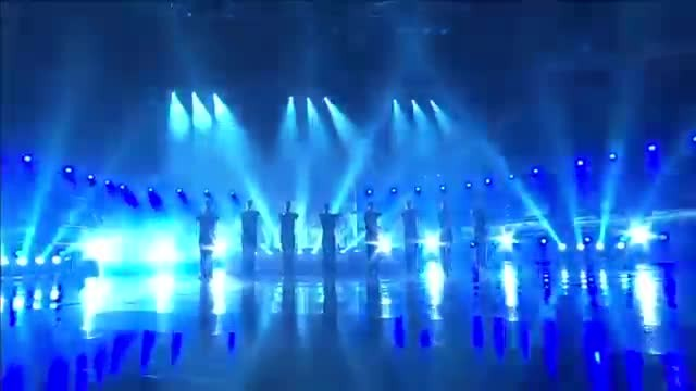 9 Men line up to dance but notice man in front when woman with drums enter stage