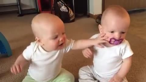Mom grabs the camera quickly to record cutest fight ever between her twins