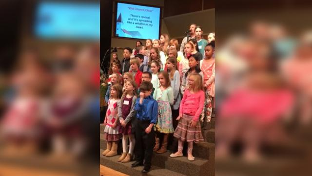 Little girl sings and dances in church choir