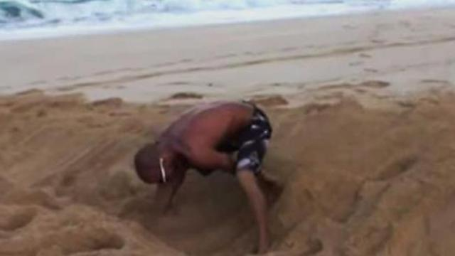 He digs a hole in the sand. When the waves hit, everyone stares in disbelief