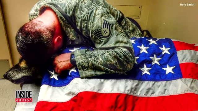 Soldier says goodbye to hero dog - drapes American flag over him